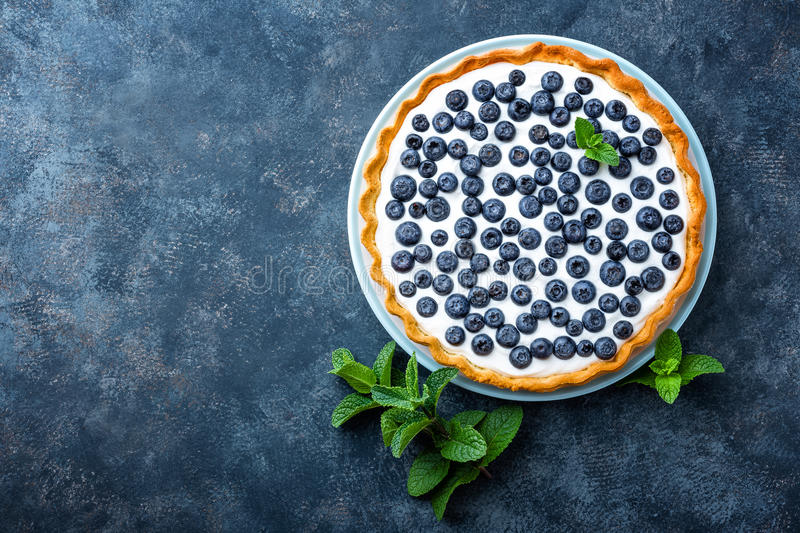 Delicious dessert blueberry tart with fresh berries and whipped cream, sweet tasty cheesecake, berry pie royalty free stock images