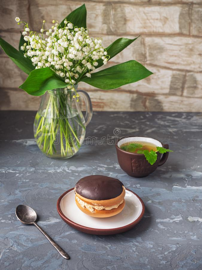 Delicious dessert of bush cake and green tea with mint, a bouquet of lily of the valley for the mood stock photo
