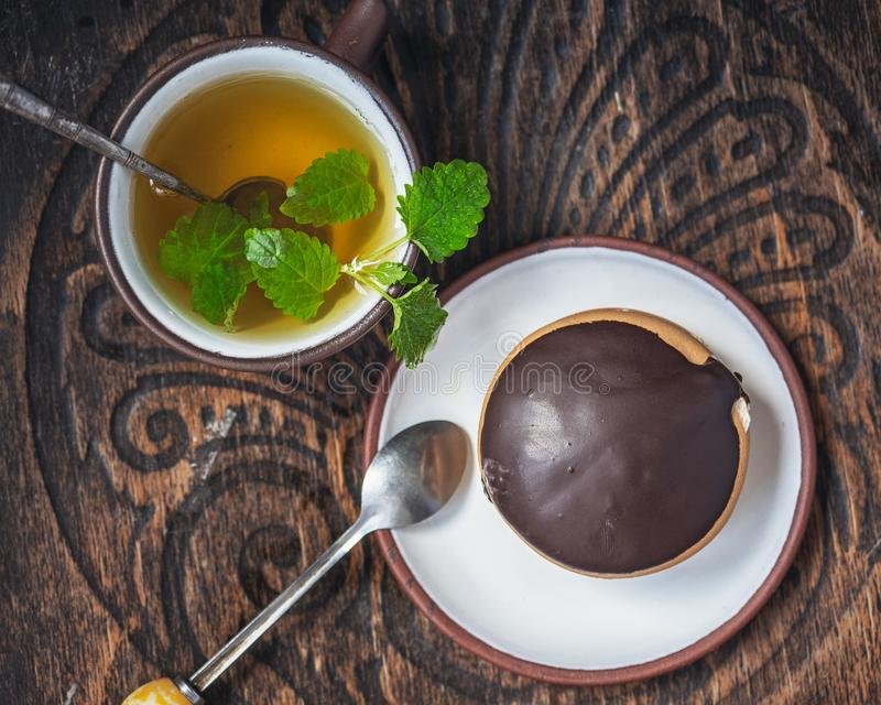 Delicious dessert of bush cake and green tea with mint are on the old chair stock photos