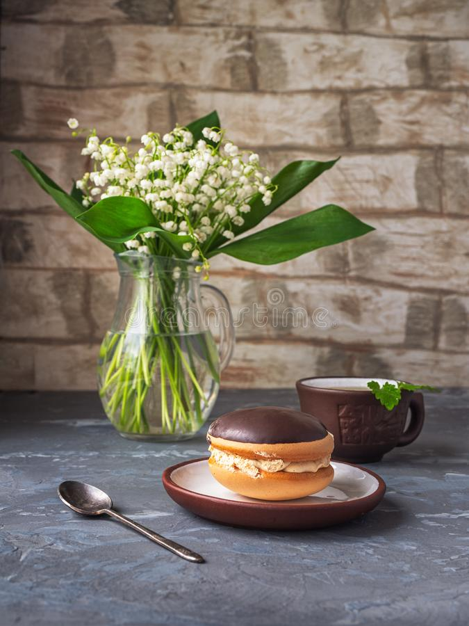 Delicious dessert of cake bush and green tea with mint, spring bouquet of fragrant lilies of the valley in a glass jug stock photos