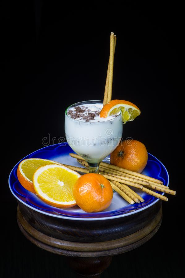 Milky dessert with fruit and grated chocolate on a plate in a glass royalty free stock photos