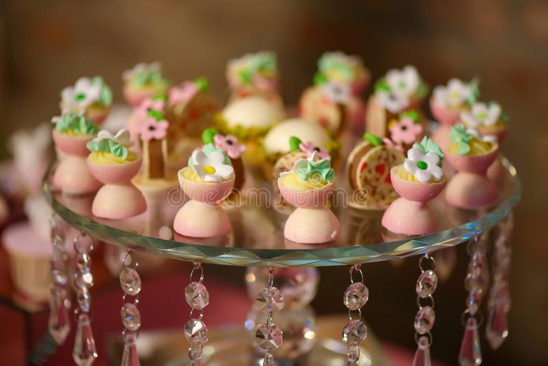 Dessert variety of playful or themed bite-sized cakes shaped as small white and pink chocolate cups with icing sugar flowers stock photo