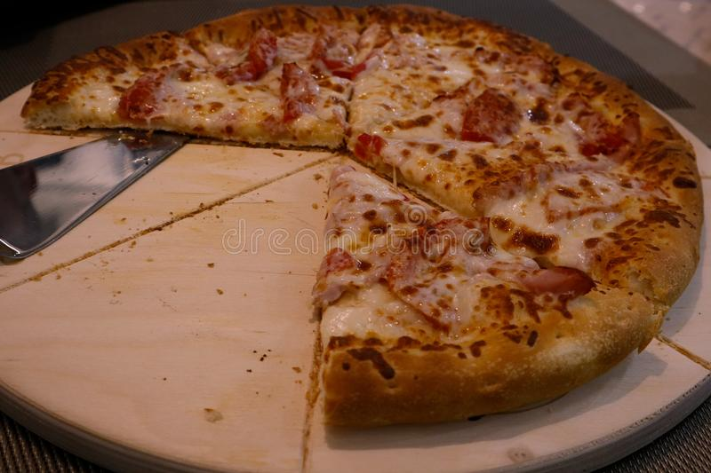 Delicious dinner, juicy pizza with cheese, tomatoes and meat on a wooden tray stock images
