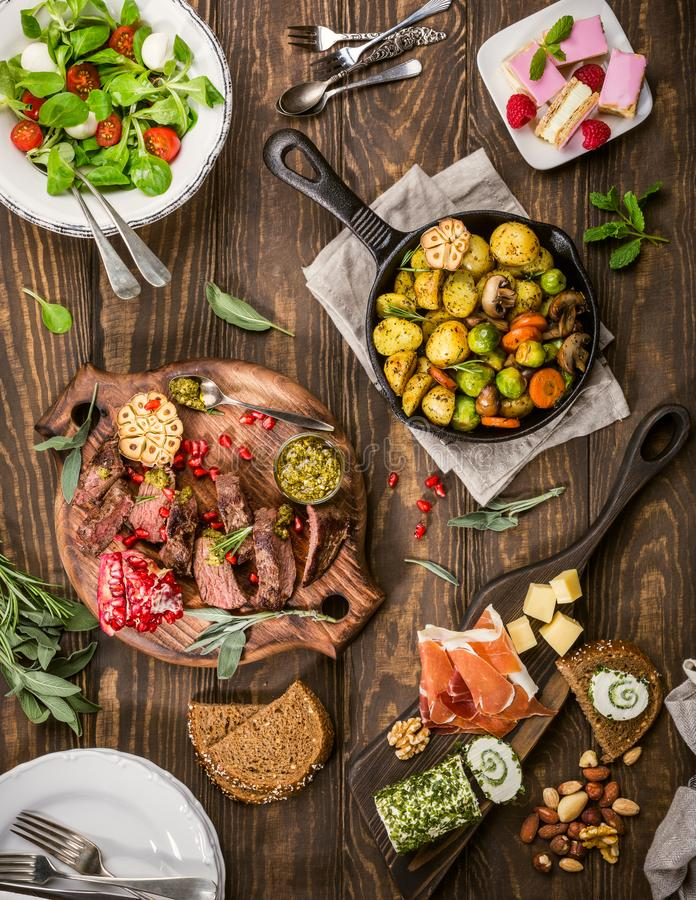 Delicious dinner table. Flat lay of delicious dinner table with roasted meat steak, appetizers and desserts. Top view. Healthy food concept stock photography
