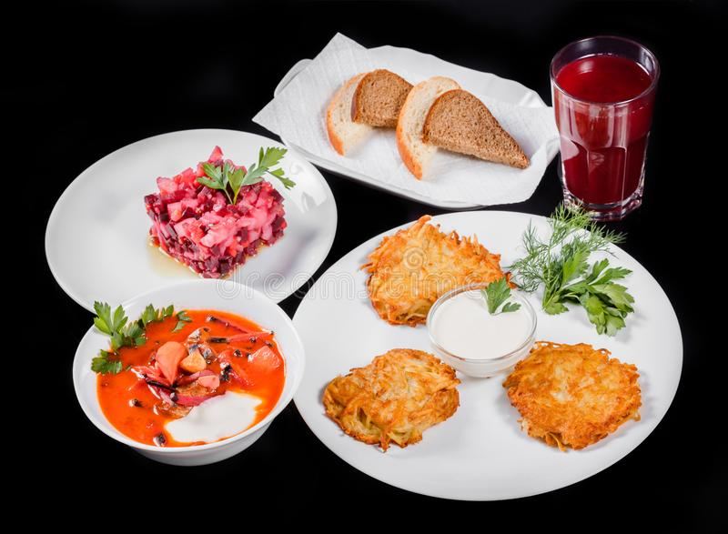 Delicious dinner table with potato pancakes, traditional beetroot soup - borscht with beef, beet salad Vinaigrette.  stock image