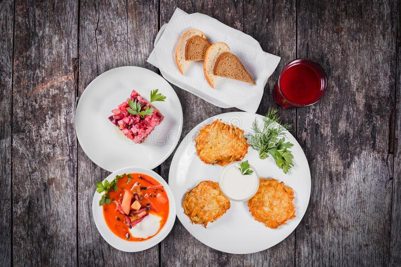 Delicious dinner table with potato pancakes, traditional beetroot soup - borscht with beef, beet salad Vinaigrette,. Bread and compote on wooden background. Top stock photography