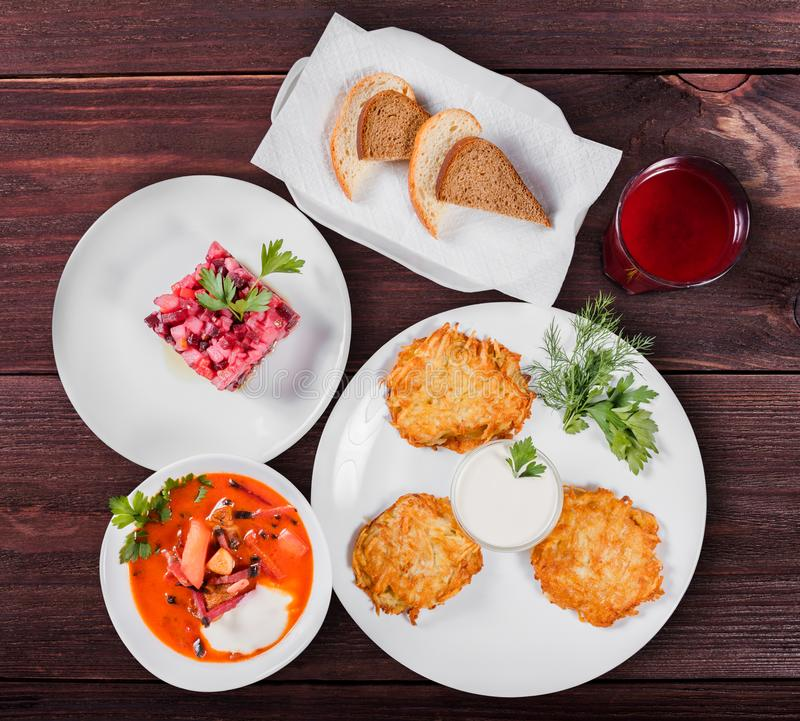 Delicious dinner table with potato pancakes, traditional beetroot soup - borscht with beef, beet salad Vinaigrette. stock photography