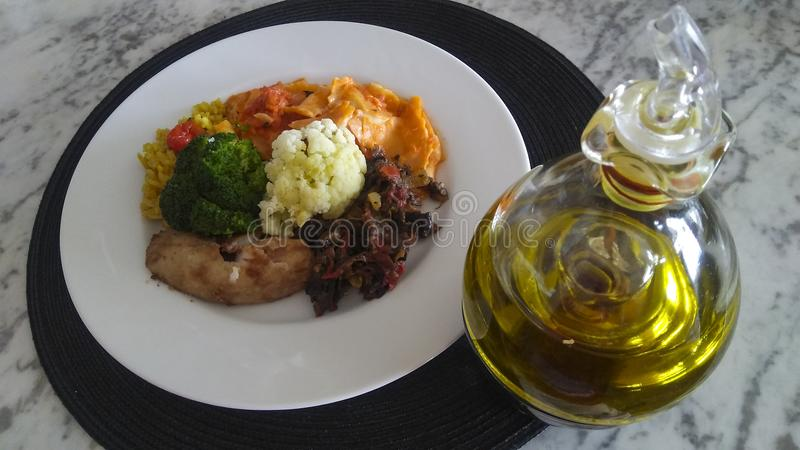 Delicious dish with ravioli, fish, eggplant, cauliflower, rice and oil stock photo