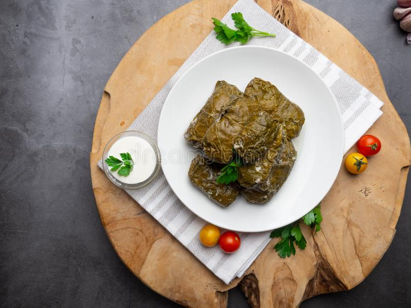 Delicious dolma sarma stuffed grape leaves rice, white yogurt sauce. Lebanese dolma sarma on plate. Lebanon turkish greek middle stock photography