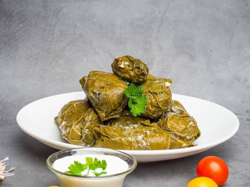 Delicious dolma sarma stuffed grape leaves rice, white yogurt sauce. Lebanese dolma sarma on plate. Lebanon turkish greek middle stock images