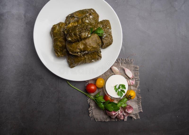 Delicious dolma sarma stuffed grape leaves rice, white yogurt sauce. Lebanese dolma sarma on plate. Lebanon turkish greek middle eastern cuisine. Dinner food royalty free stock photography