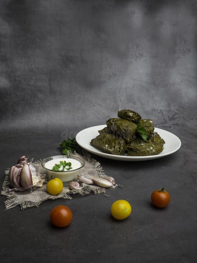 Delicious dolma sarma stuffed grape leaves rice, white yogurt sauce. Lebanese dolma sarma on plate. Lebanon turkish greek middle eastern cuisine. Dinner food royalty free stock image