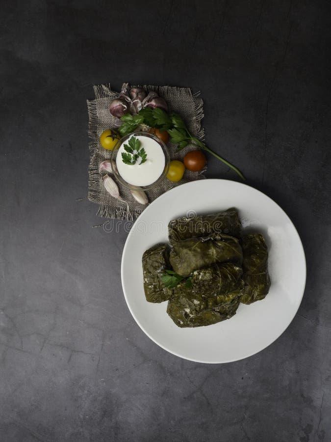 Delicious dolma sarma stuffed grape leaves rice, white yogurt sauce. Lebanese dolma sarma on plate. Lebanon turkish greek middle eastern cuisine. Dinner food stock photo