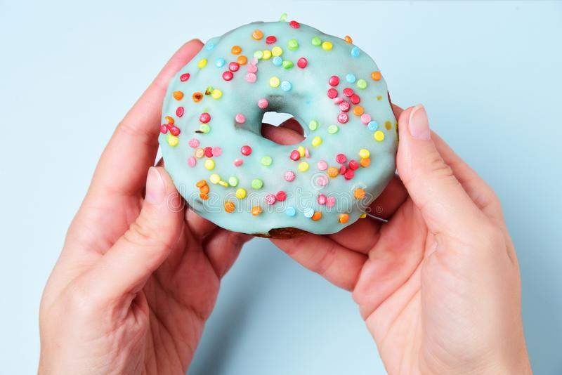 Delicious donut covered with blue glaze in female hand on blue b. Ackground royalty free stock photo