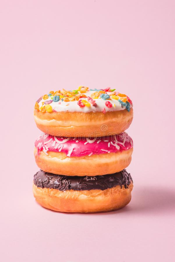 Delicious donuts for birthday on pastel pink background. royalty free stock photography