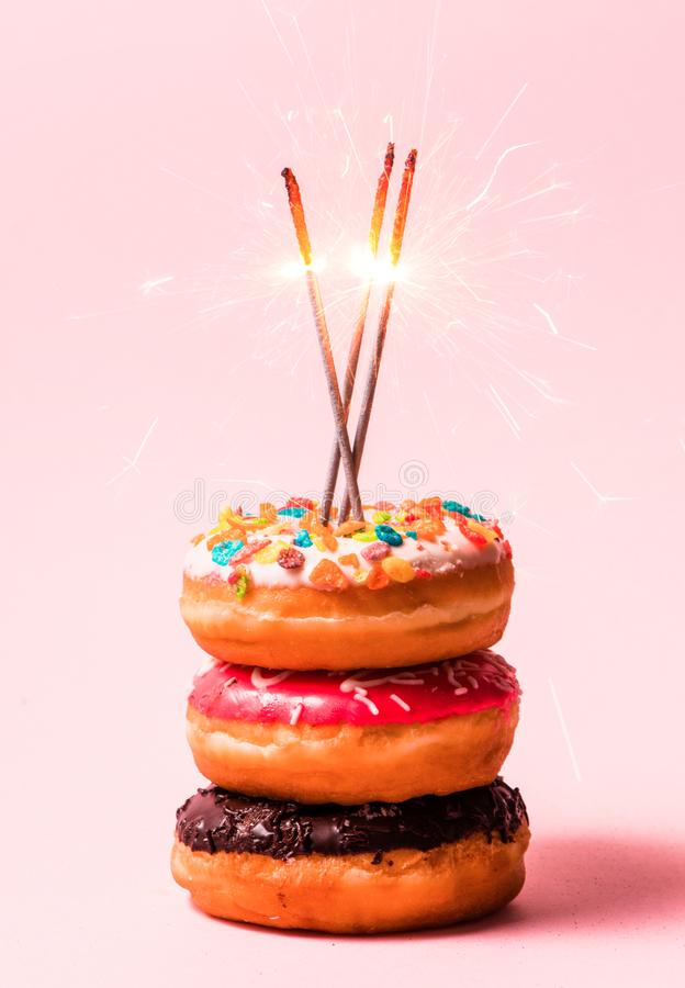 Delicious donuts for birthday on pastel pink background. royalty free stock images