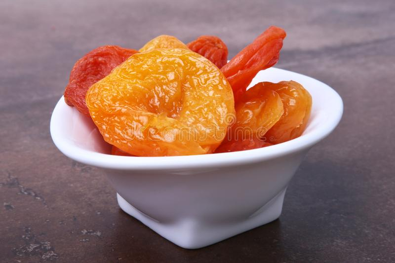 Delicious dried organic apricots in bowl isolated on stone table. stock photo
