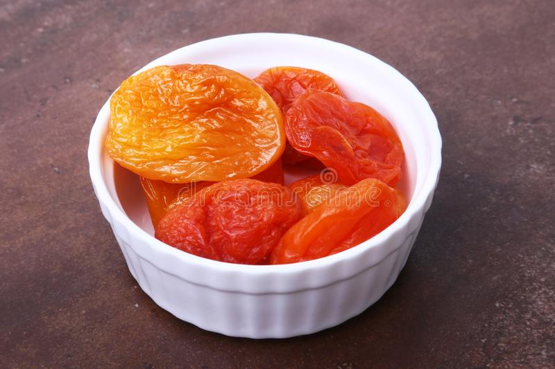 Delicious dried organic apricots in bowl isolated on stone table. stock photos