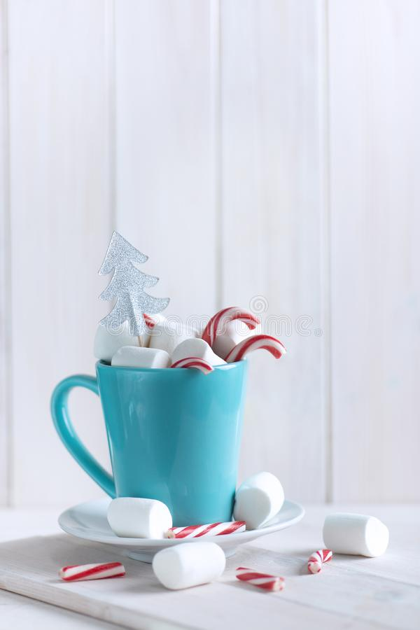Delicious drink with marshmallows and Christmas candy can on table stock photos