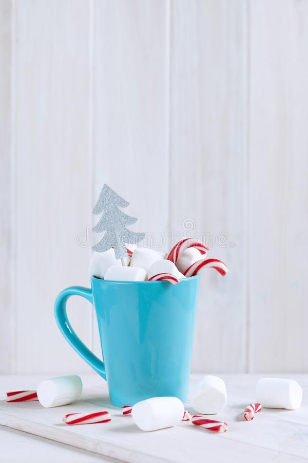 Delicious drink with marshmallows and Christmas candy can on table royalty free stock image