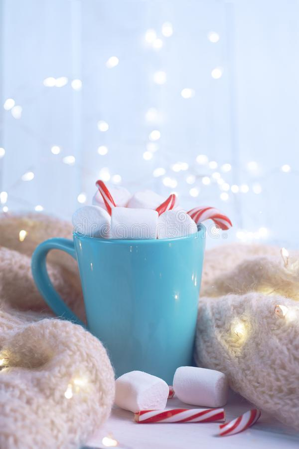 Delicious drink with marshmallows and Christmas candy can on table stock photo