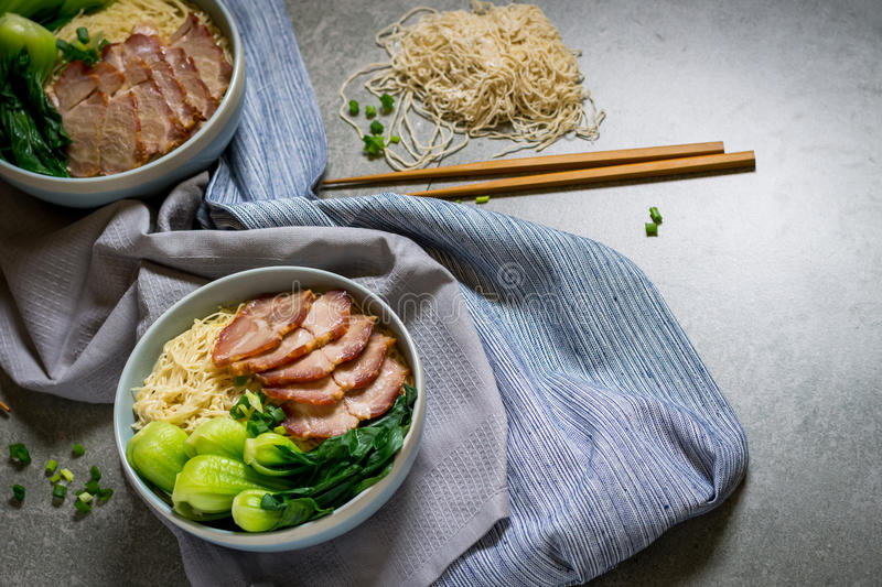 Delicious egg noodle with red pork and vegetable in bowl. Decoration with chopstick on table,thaifood,selective focus stock photography