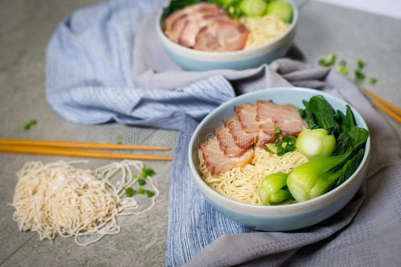 Delicious egg noodle with red pork and vegetable in bowl. Decoration with chopstick on table,thaifood,selective focus stock images