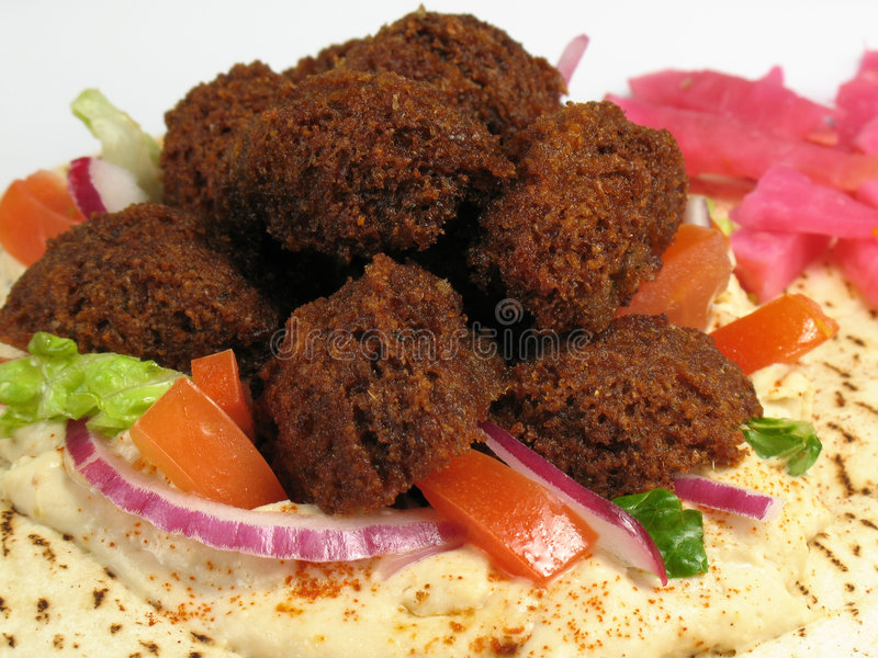 Delicious Falafels and Pita Br. A delicious portion of falafels served on top of a pita bread with hummus, lettuce, tomato, red onions, and a side of turnips royalty free stock photo