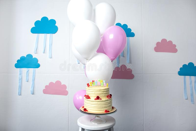 delicious festive cake with happy birthday lettering and balloons in decorated room stock image