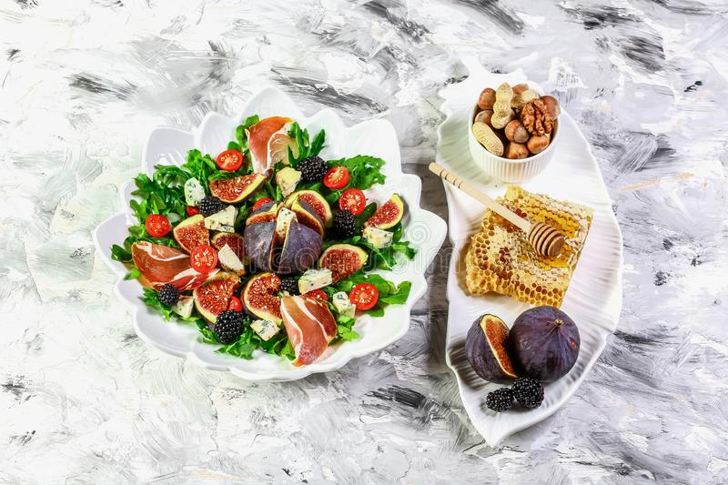 Delicious figs, arugula, goat cheese and pecan nuts salad, low carbs ingredients for healthy eating concept and weight loss. top royalty free stock image