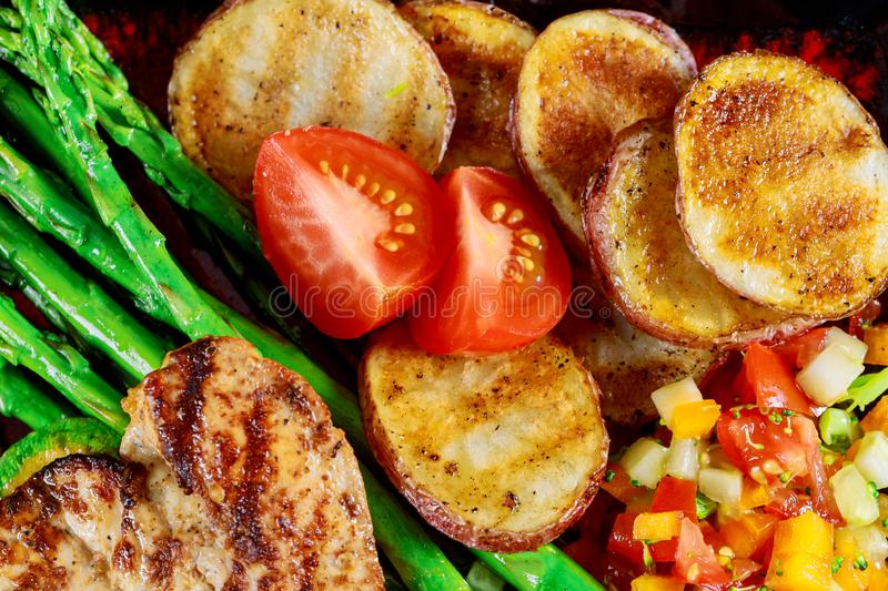 Delicious fillet chicken breast grilled with potato chips, zucchini and asparagus on top view royalty free stock photo
