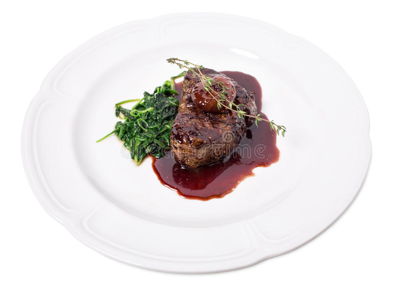 Delicious fillet mignon steak with chard. Delicious grilled fillet mignon steak with chard covered with red wine sauce. Isolated on a white background stock photo