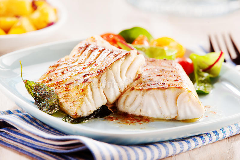 Delicious fillets of pollock or coalfish. Cooked in a spicy marinade and served with fresh salad and baby potatoes as a seafood appetizer to dinner stock photography