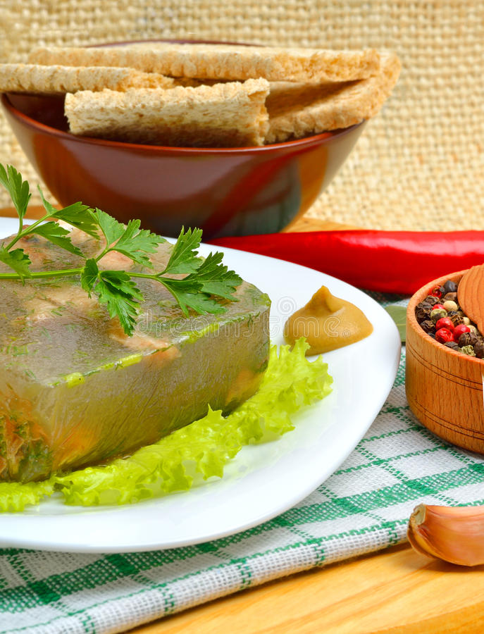 Delicious fish aspic on white plate with mustard and green salad royalty free stock photos