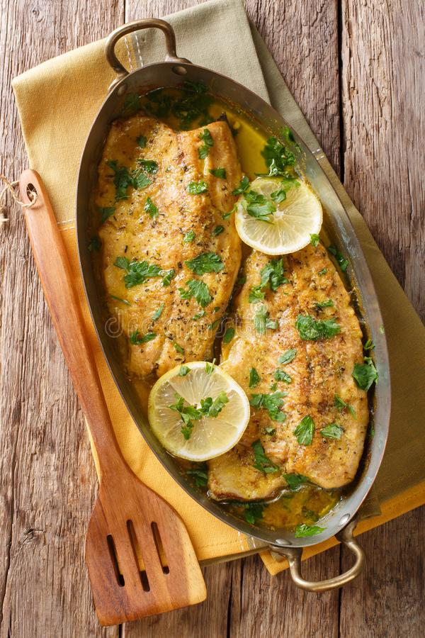 Delicious fish: baked trout fillets with garlic buttery herb sauce, lemon and parsley close-up in a copper pan. Vertical top view stock photos