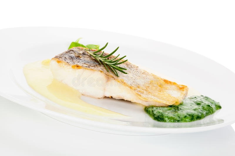 Delicious fish eating. Fresh perch fish fillet with potato and vegetable sauce on white plate on white. Exquisite eating, fine gastronomy stock image