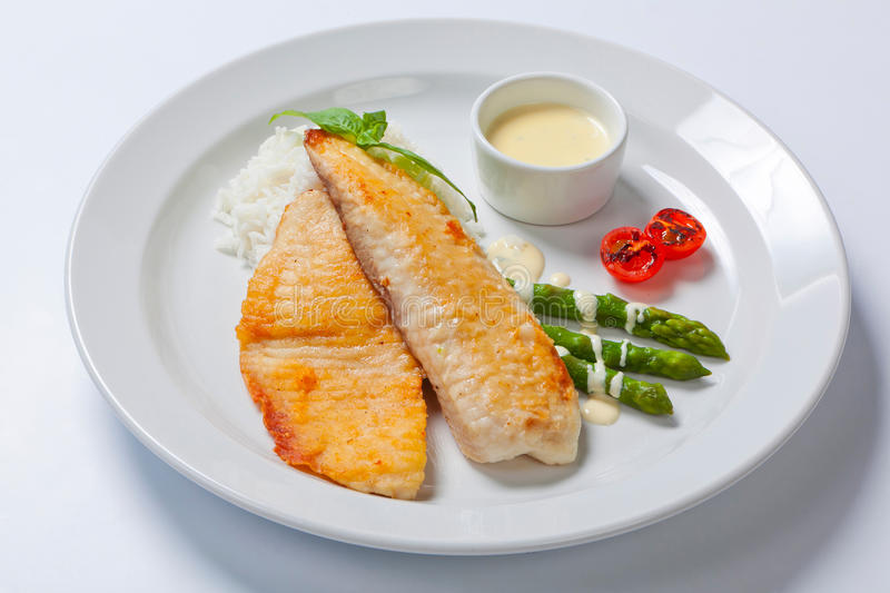 Delicious fish steak with green asparagus and rice. And sauce royalty free stock photography