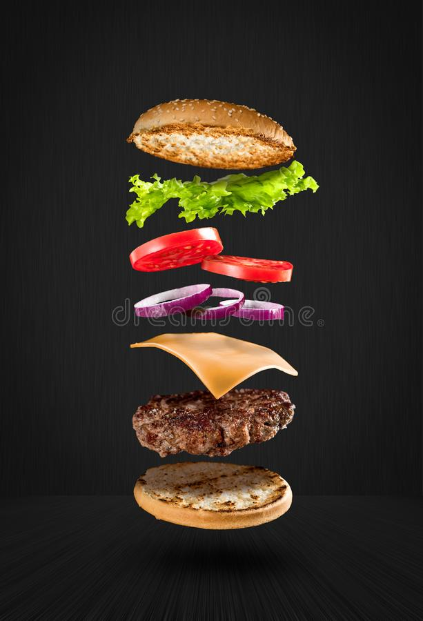 Delicious flying hamburger. Delicious hamburger with flying ingredients on black background stock image