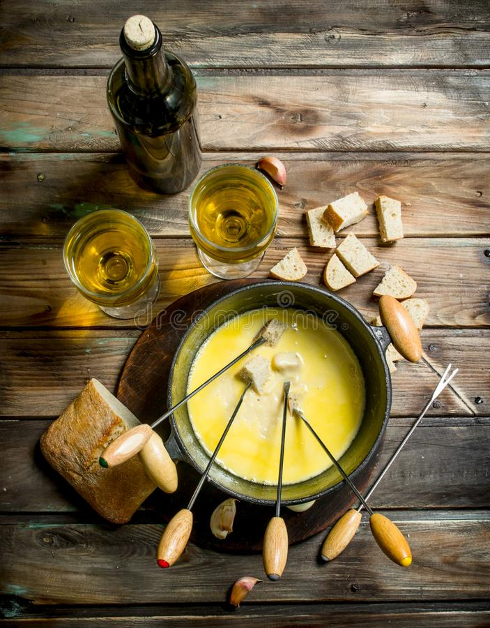 Delicious fondue cheese with bread slices and white wine. On a wooden background stock photography