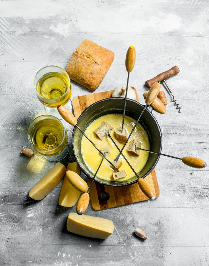 Delicious fondue cheese with bread and white wine. On rustic background stock images