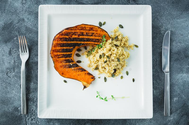 Delicious food - baked pumpkin with sprouted millet and pumpkin grains on the dark table. Flat lay. Top view. Delicious food - baked pumpkin with sprouted millet royalty free stock photo