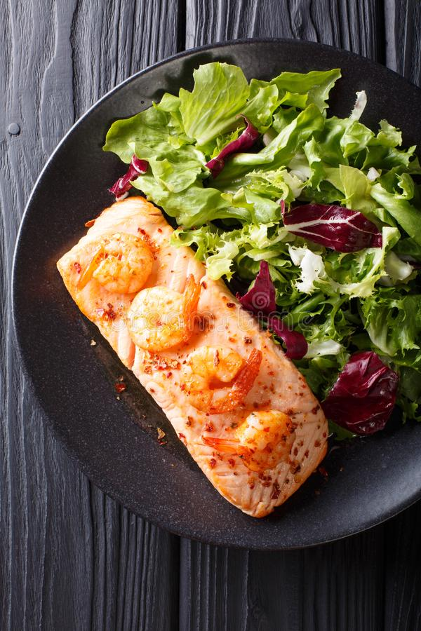 Delicious food: baked salmon with prawns in honey sauce and fresh salad on a plate close-up. Vertical top view. Delicious food: baked salmon with prawns in honey stock photography