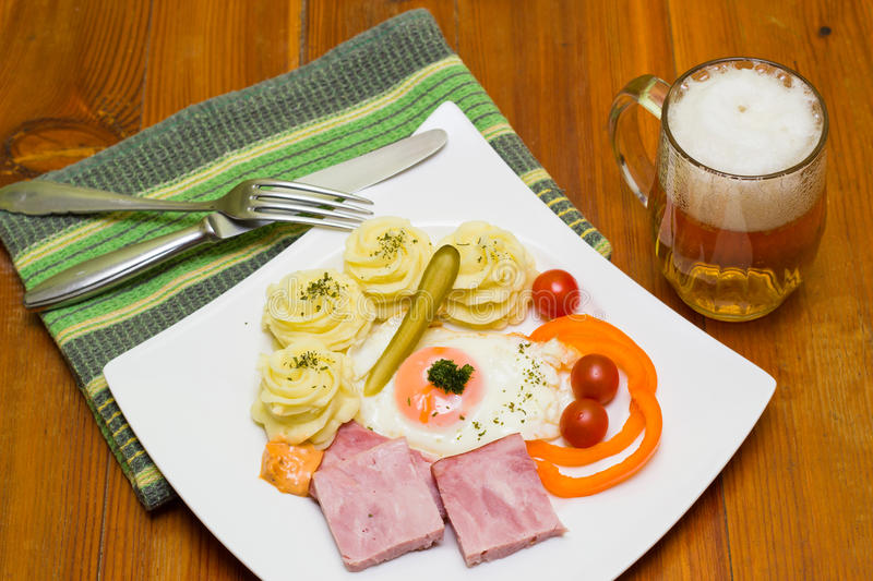 Delicious food. Smoked meat, fried egg and mashed potatoes on white plate and a beer in glass mug stock photos