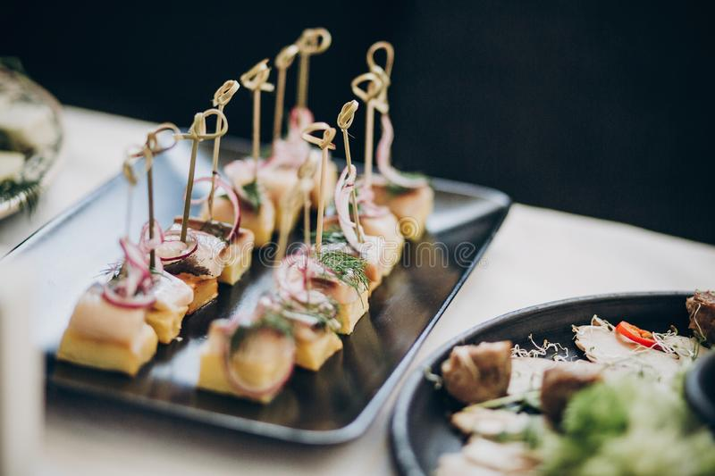 Delicious food table at wedding reception. Fish finger appetizers with onion on table at wedding or christmas feast. Luxury stock images