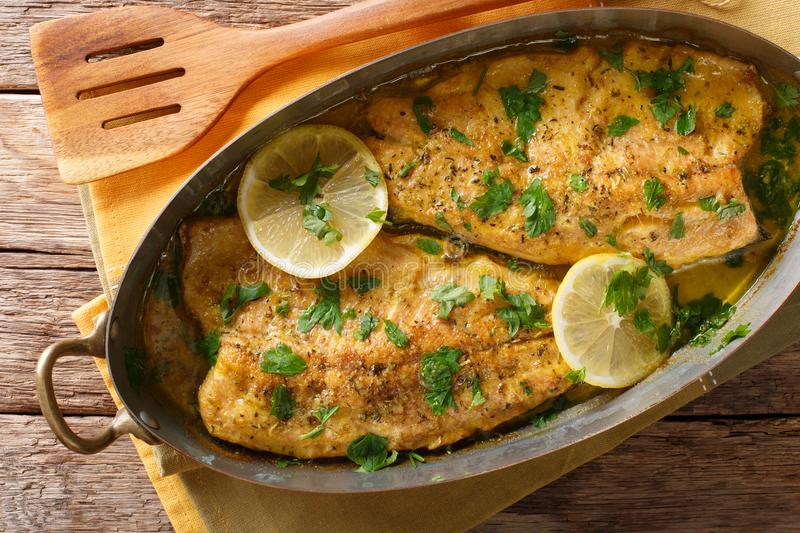 Delicious food: trout fish with garlic lemon butter sauce, parsley close-up in a copper frying pan. horizontal top view. Delicious food: trout fish with garlic royalty free stock images