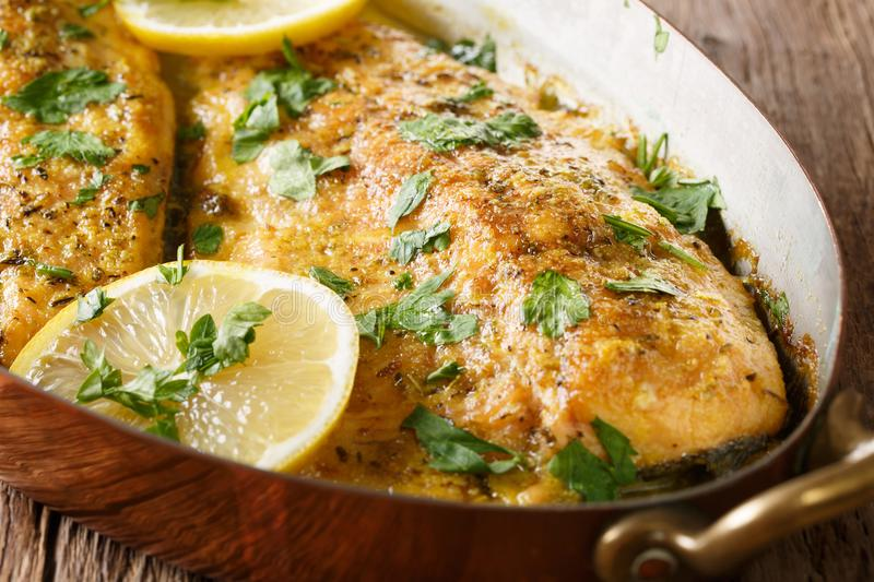 Delicious food: trout fish with garlic lemon butter sauce, parsley close-up in a copper frying pan. horizontal. Delicious food: trout fish with garlic lemon stock photo