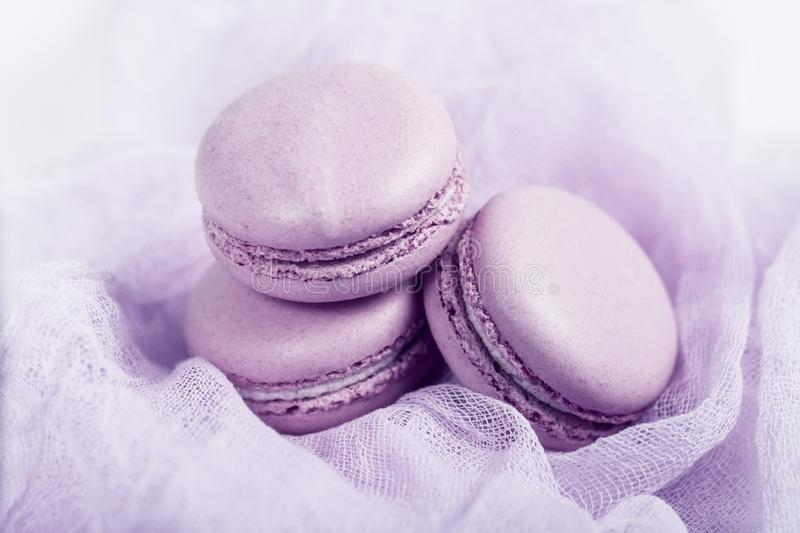 Delicious french dessert. Three gentle soft pink cakes  macaron or macaroon on airy fabric stock photography