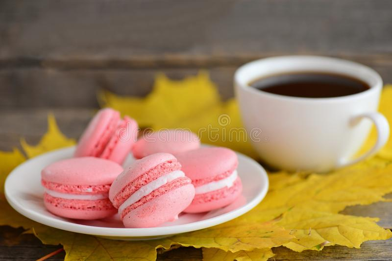Delicious French macarons. Light pink macarons on a white plate, a cup of coffee, yellow leaves on an old wooden background royalty free stock photography