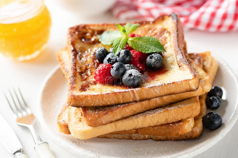 Delicious french toast with berries and honey. Closeup view. Traditional sweet breakfast food royalty free stock image