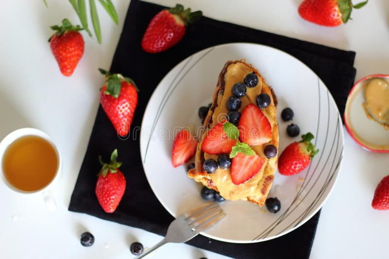 Delicious french toasts with berries, agave syrup and peanut butter in plate for breakfast on white table, top view. royalty free stock photos